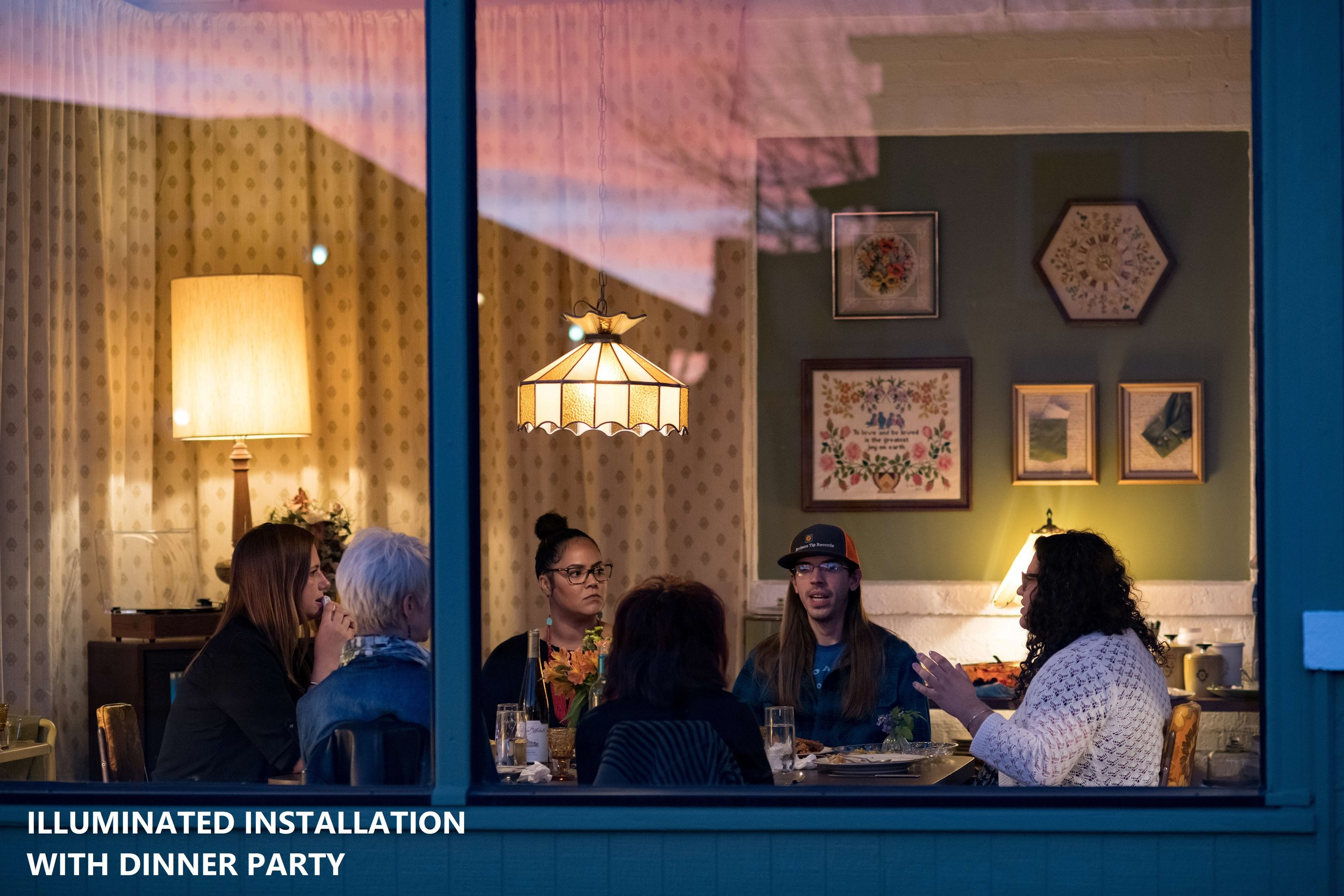"""Illuminated"" is a small installation of an intimate dining room that offered weekly potluck dinner parties to spark conversations and share memories over food and fellowship. Set in a glassed-in former gas station, the nostalgic space provided public glimpses of private moments.  OL Guild, Valley Junction, West Des Moines, Iowa, in Spring 2019"