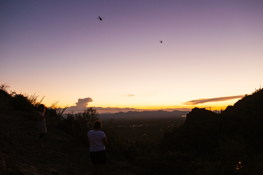 Barely enough light to see much of Saguaro National Park. Spectators watch military helicopters fly over.