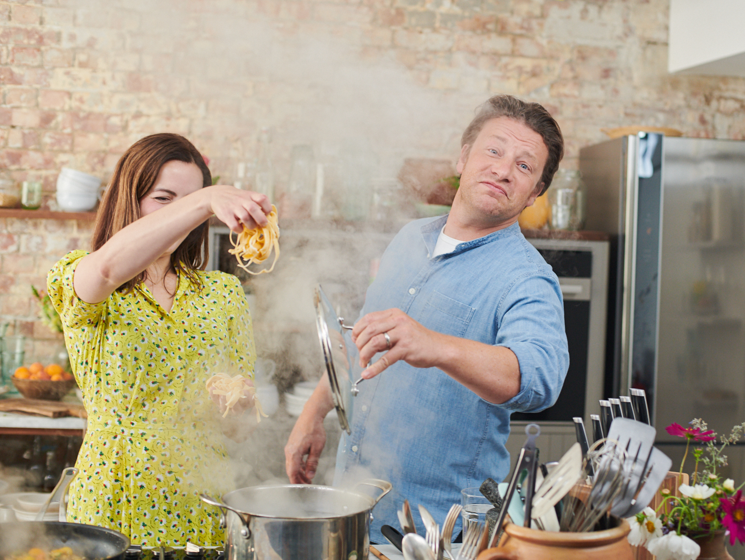 Jamie Oliver in his HQ in London, Showing Rosamund Dean some recepies.