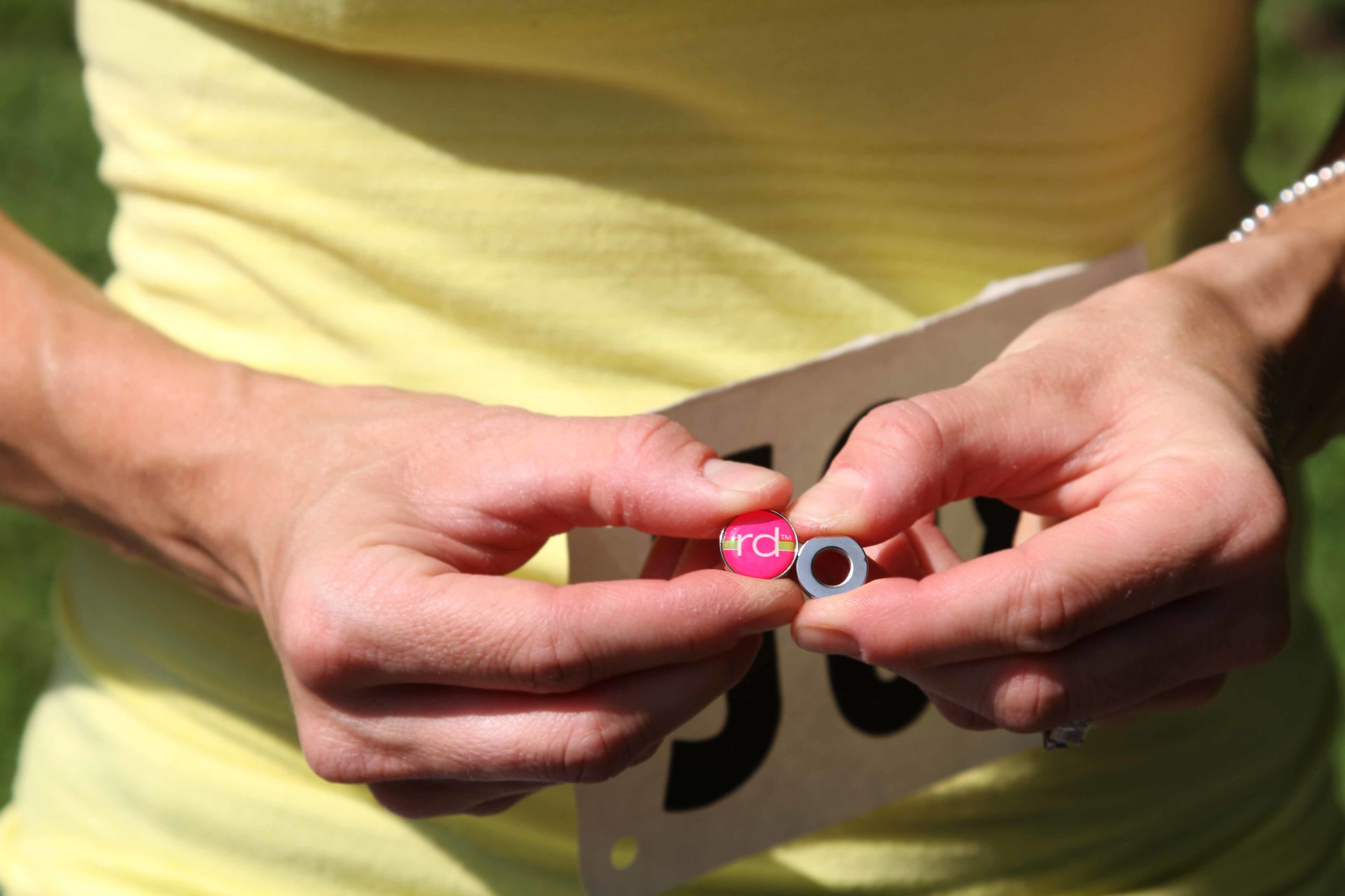 RaceDots consist of two magnets that lock together to securely hold a race number in place without damaging clothing