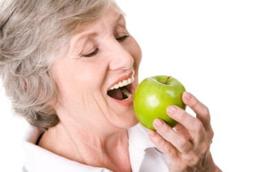 Woman with removable dentures biting an apple