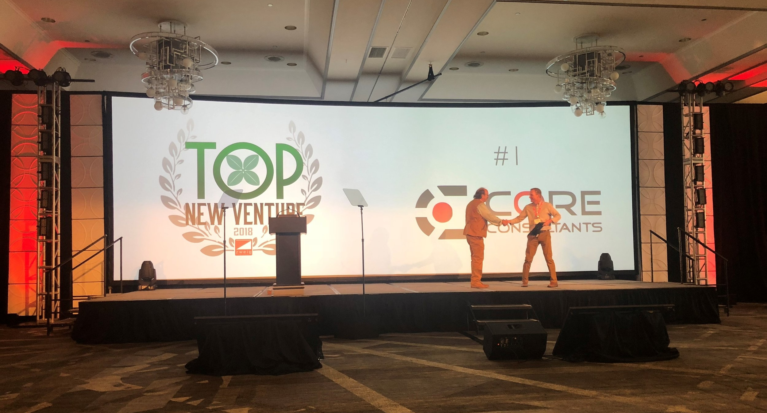 Blake Calvert (right), CORE President & CEO accepting Zweig Group's Top New Venture Award from Mark Zweig (left) at the Hot Firm Conference in Dallas, TX.