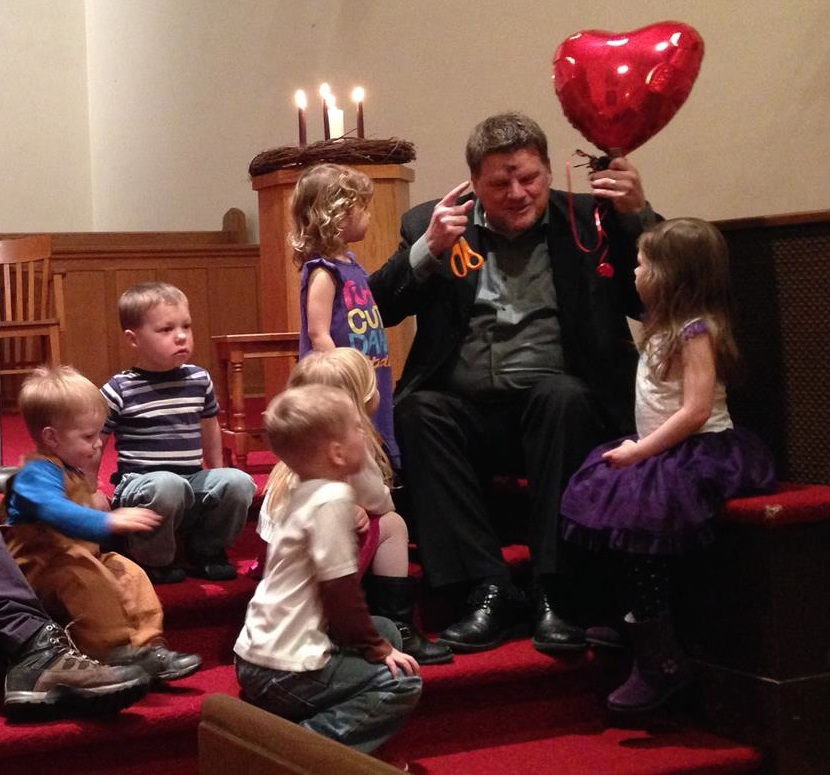 Children listening to Pastor Ron at an Ash Wednesday evening service