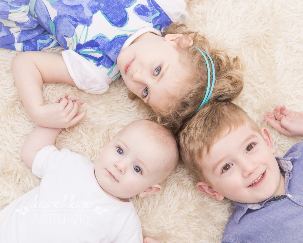 A family portrait captured in studio by Laurel Lane Photography, a photographer based in Macclesfield, Cheshire of a three children lying down looking at the camera - siblings.