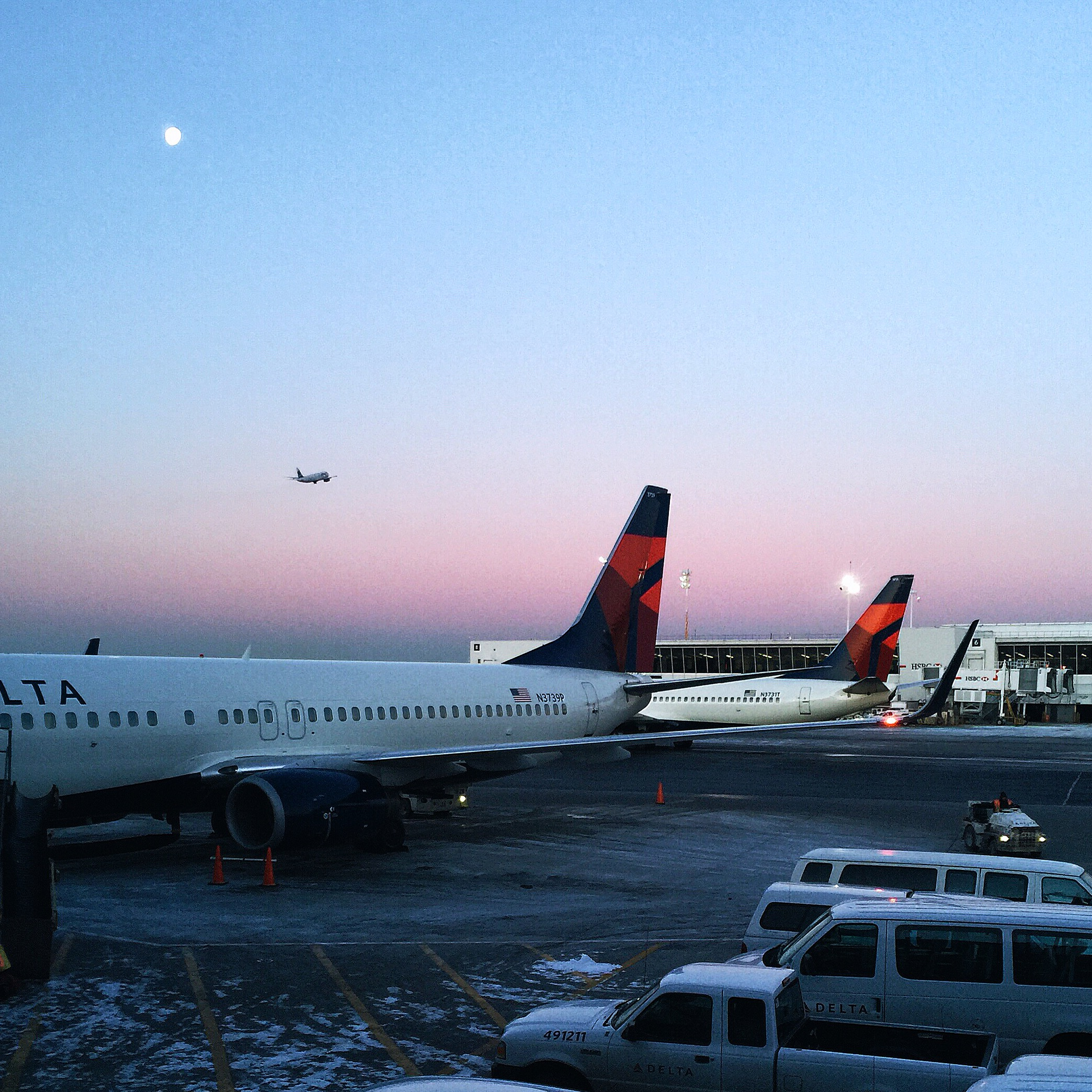 {the sunrise at JFK featuring the moon and a miniature airplane taking off.}