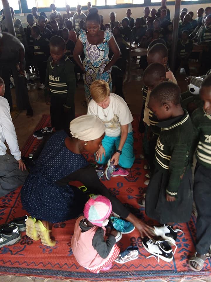 Iqweonu Ekene Loretta and Leslie helping with shoes.jpg