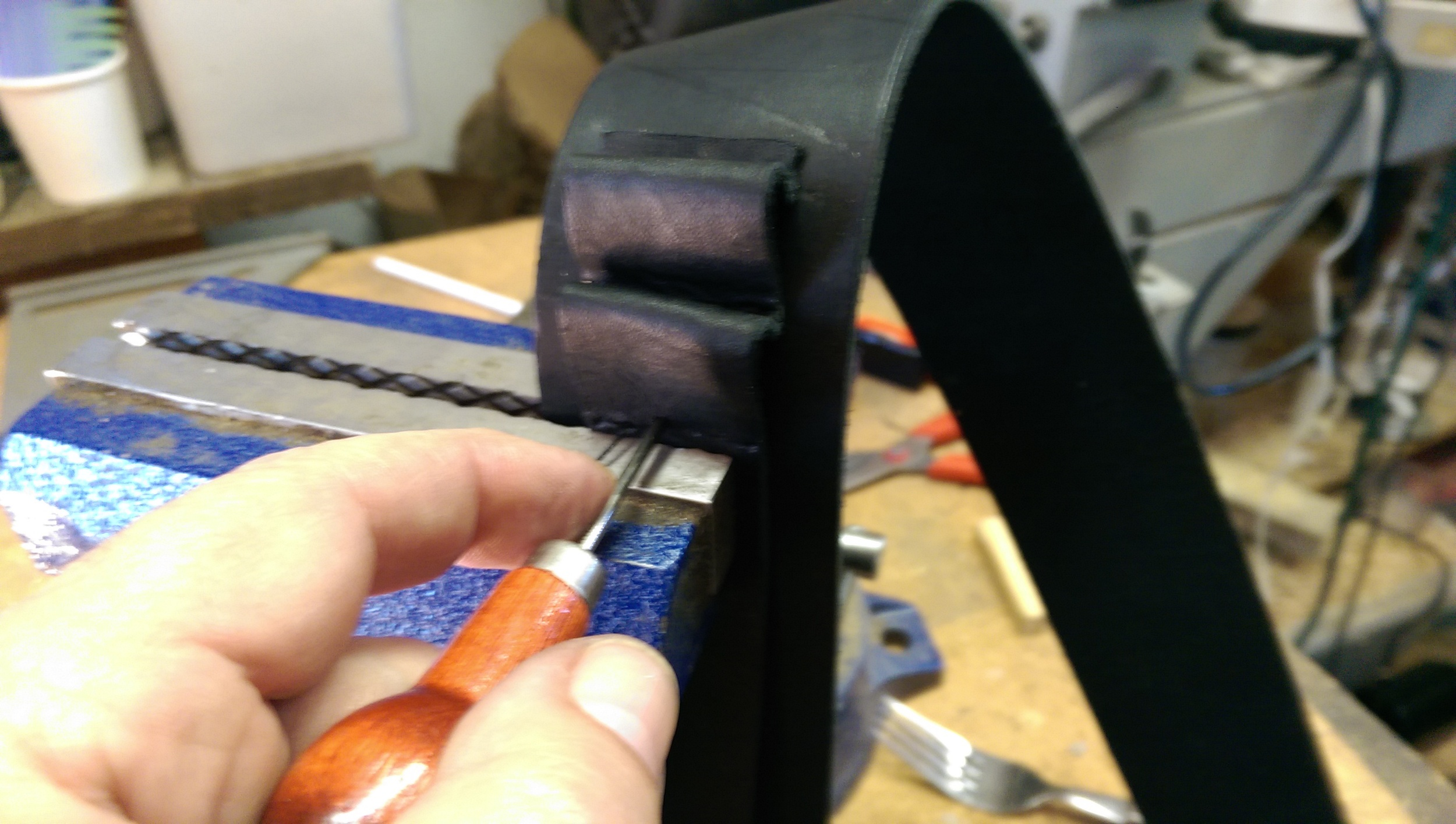 Aligning the spacing lines on the straps and then akligning to the vice jaws in order to punch the stitching holes