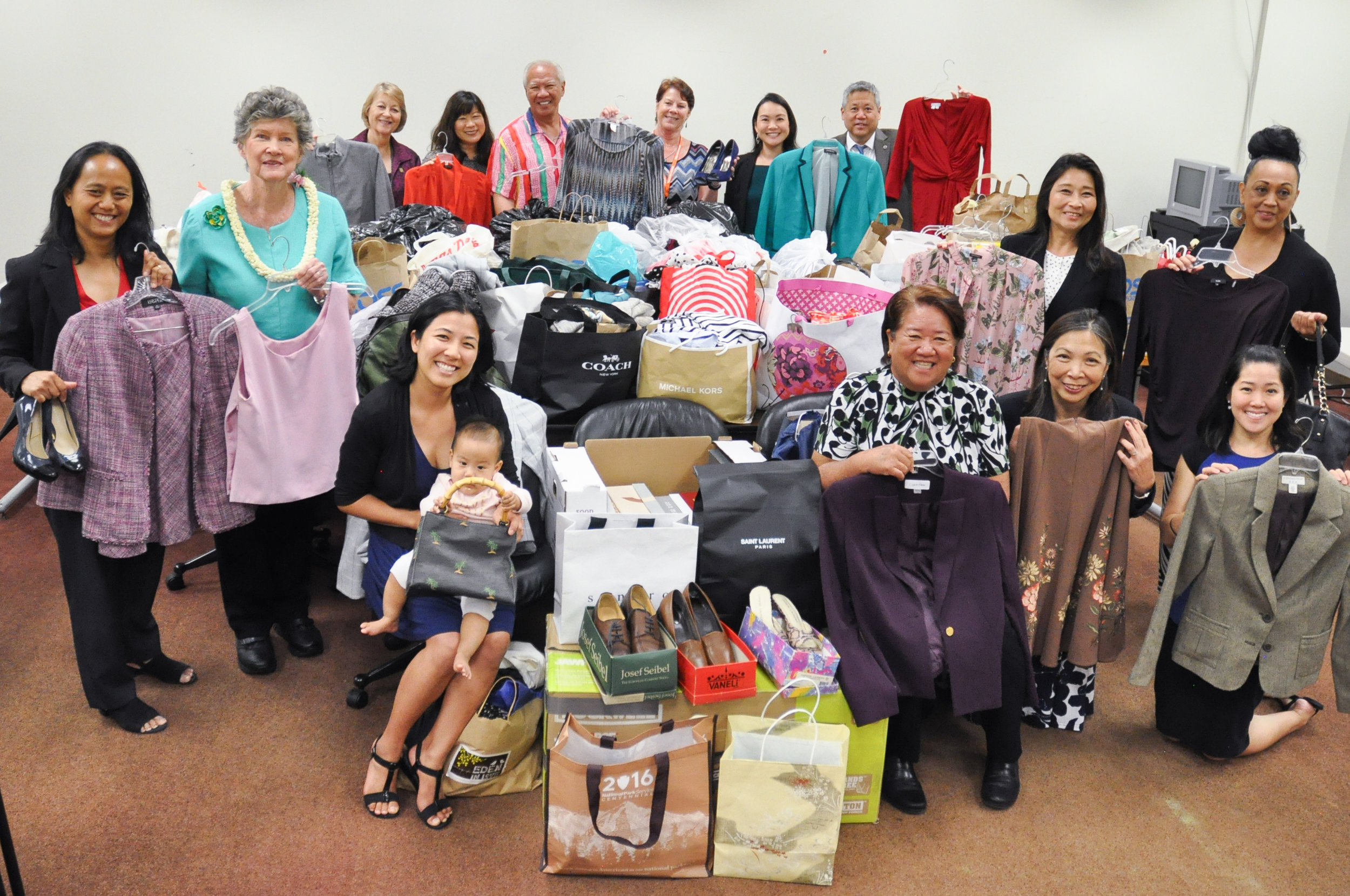Lawmakers, including members of the Women's Legislative Caucus, collected 432 pounds of gently used professional clothing for the YWCA's Dress for Success program. (Standing, from left) Rep. Della Au Belatti, Rep. Cynthia Thielen, Sen. Rosalyn H. Baker, Rep. Nadine K. Nakamura, Rep. Gregg Takayama, Maryann Bray, YWCA Lead Member Services Associate, Rep. Lisa Kitagawa, House Speaker Scott K. Saiki, Rep. Sylvia Luke, Kepola Dudoit, YWCA resident artist, (seated from left) Rep. Linda Ichiyama (with baby Emily), Rep. Dee Morikawa, Rep. Joy San Buenaventura, and Cecilia Fong, the YWCA Director of Fund Development.