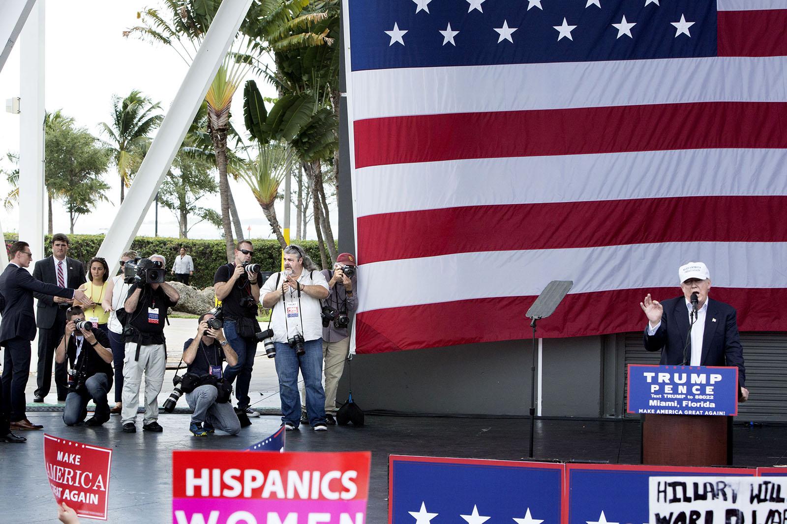 """Donald Trump håller ett tal i Miami Florida sex dagar innan presidentvalet. De fotografer som tillhör """"traveling press"""" (de som reser med kandidaten) får komma upp på scenen under några minuter i slutet av talet. De fotograferna, som nästan uteslutande jobbar för de stora amerikanska mediaorganisationerna,får alltid bättre access än de andra fotograferna på plats. Men deras arbetsgivare betalar också ganska mycket pengar för att ha dem med på det specialchartrade flygplanet som gör det möjligt att vara på alla valmöten (för oss som flyger reguljärt är det svårt att hinna med mer än ett möte per dag, speciellt de sista veckorna då kandidaterna har fyra fem valmöten per dag i olika delstater."""