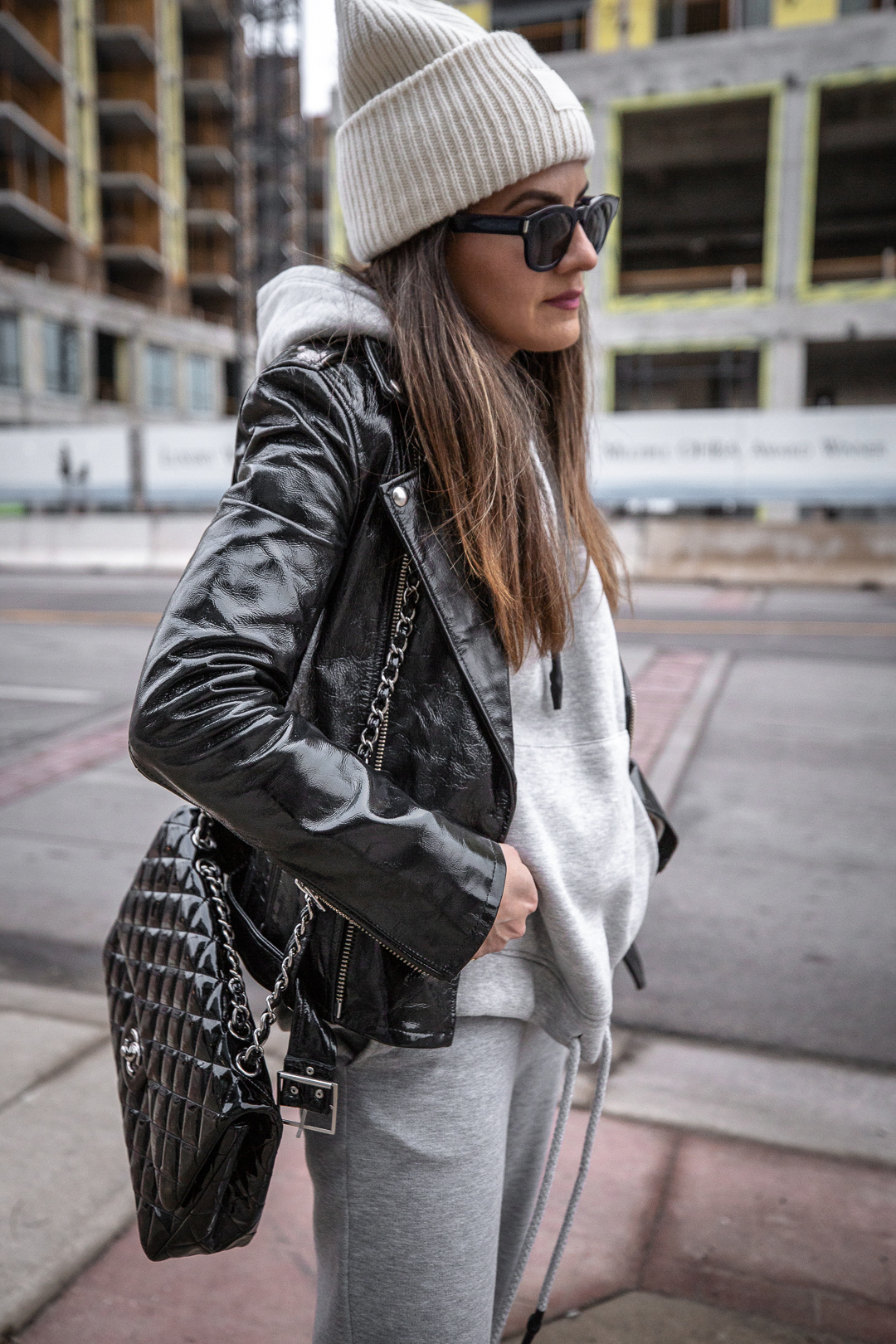 Nathalie Martin - IRO Paris patent leather moto jacket, Zara sweatsuit, grey hoodie and sweatpants, Saint Laurent white canvas logo sneakers, CHANEL patent leather jumbo flap quilted bag, ACNE studios Pansy face beanie hat - woahstyle.com_5571.jpg