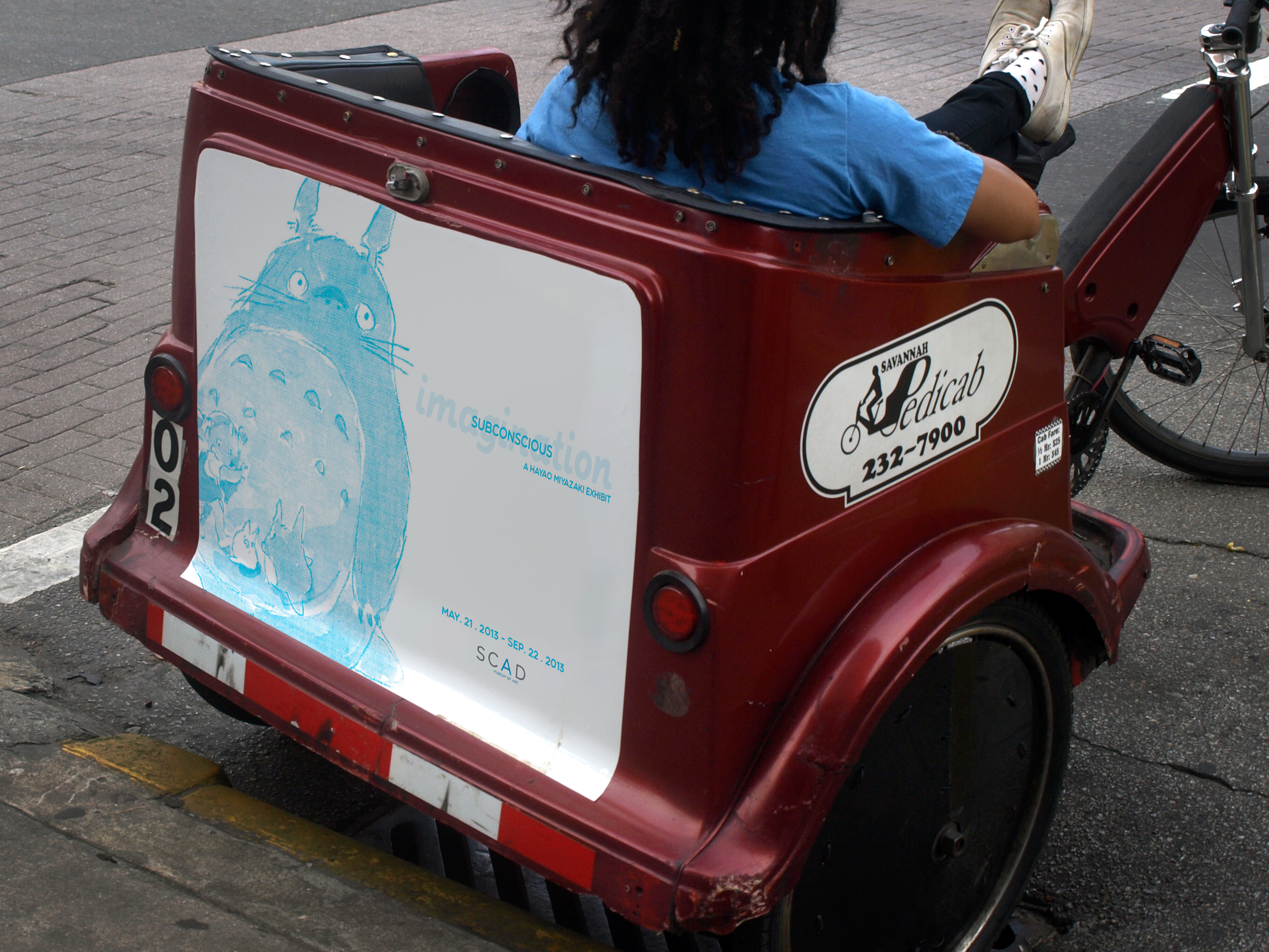 Smaller advertisement on back of pedicab, a common sight in Savannah.