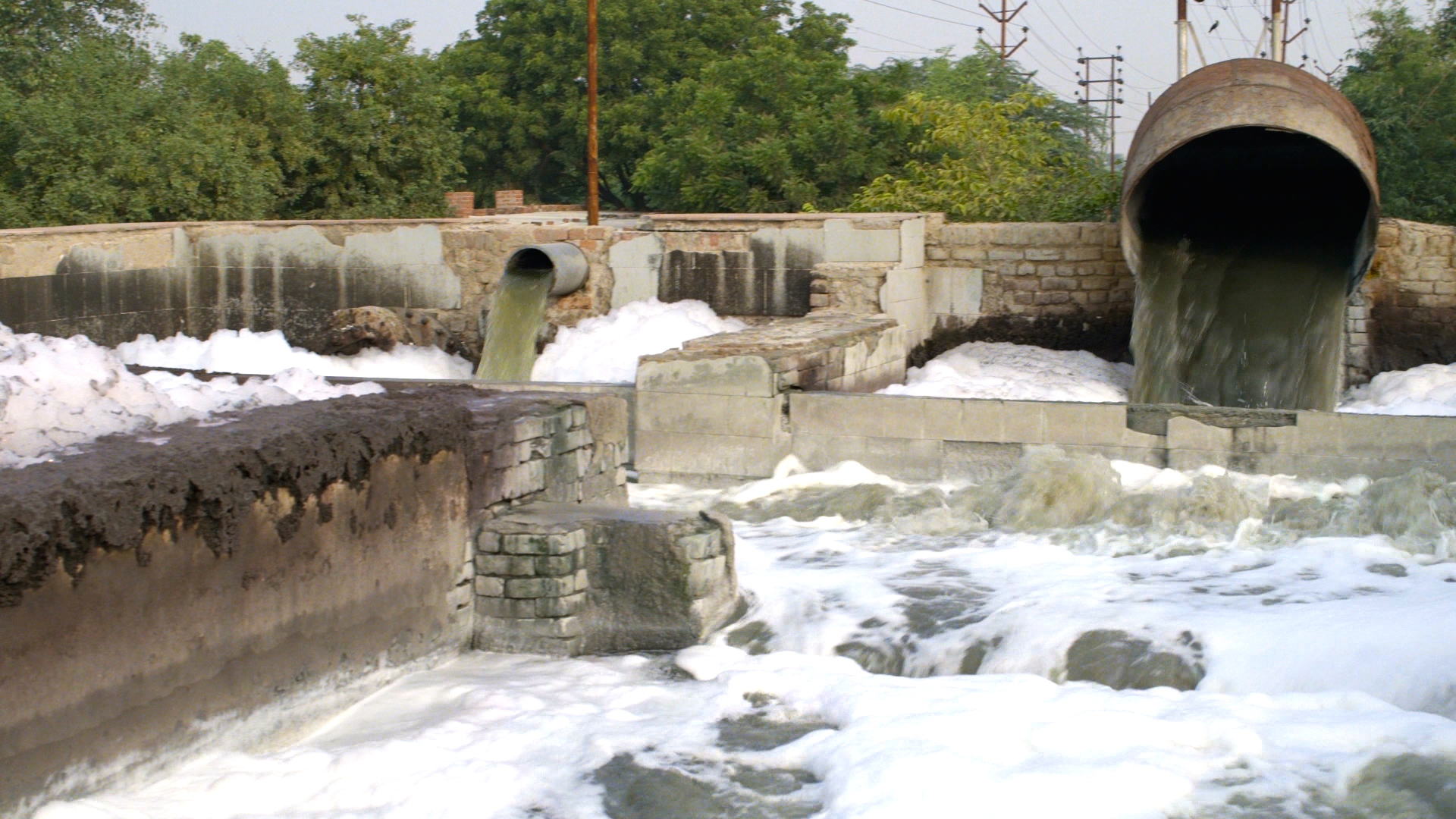 Chemical waste dumping into a flowing river next to a textile factory. Source: The True Cost