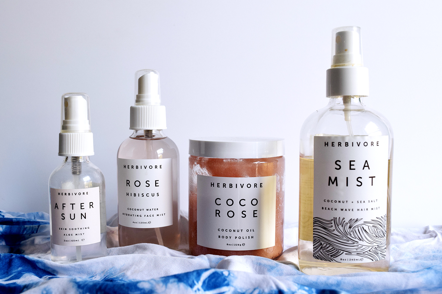 Herbivore Botanicals summer beauty products. After sun spray, rose hibiscus face mist, coco rose body scrub, sea salt hair mist dry shampoo.