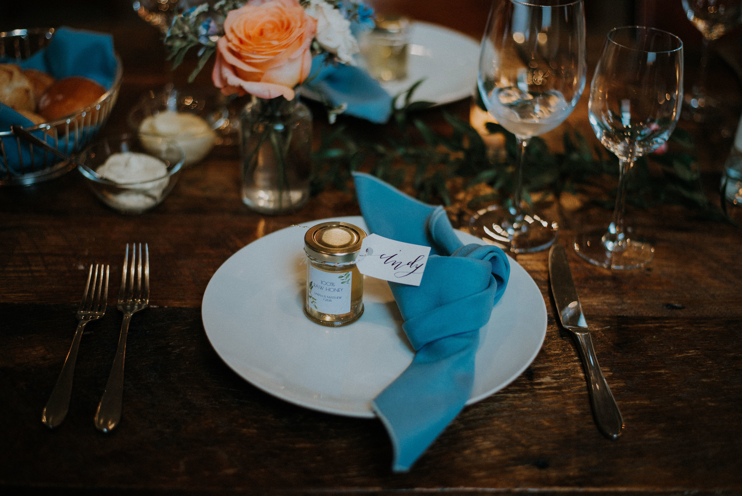 raw honey favor jar at place setting with modern calligraphy place card tag and knotted dusty blue napkin coral floral bud vases and greenery.jpg