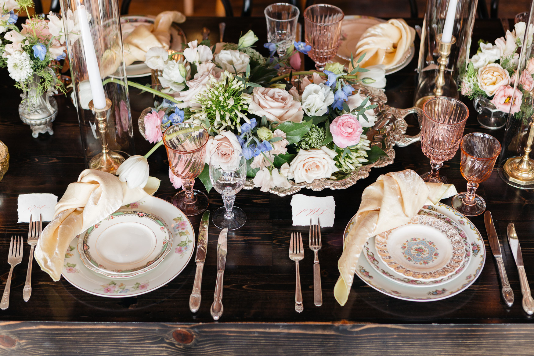 hand torn coral calligraphy on cream place cards with blush vintage goblets and dusty rose and dusty blue floral with tapers.jpg