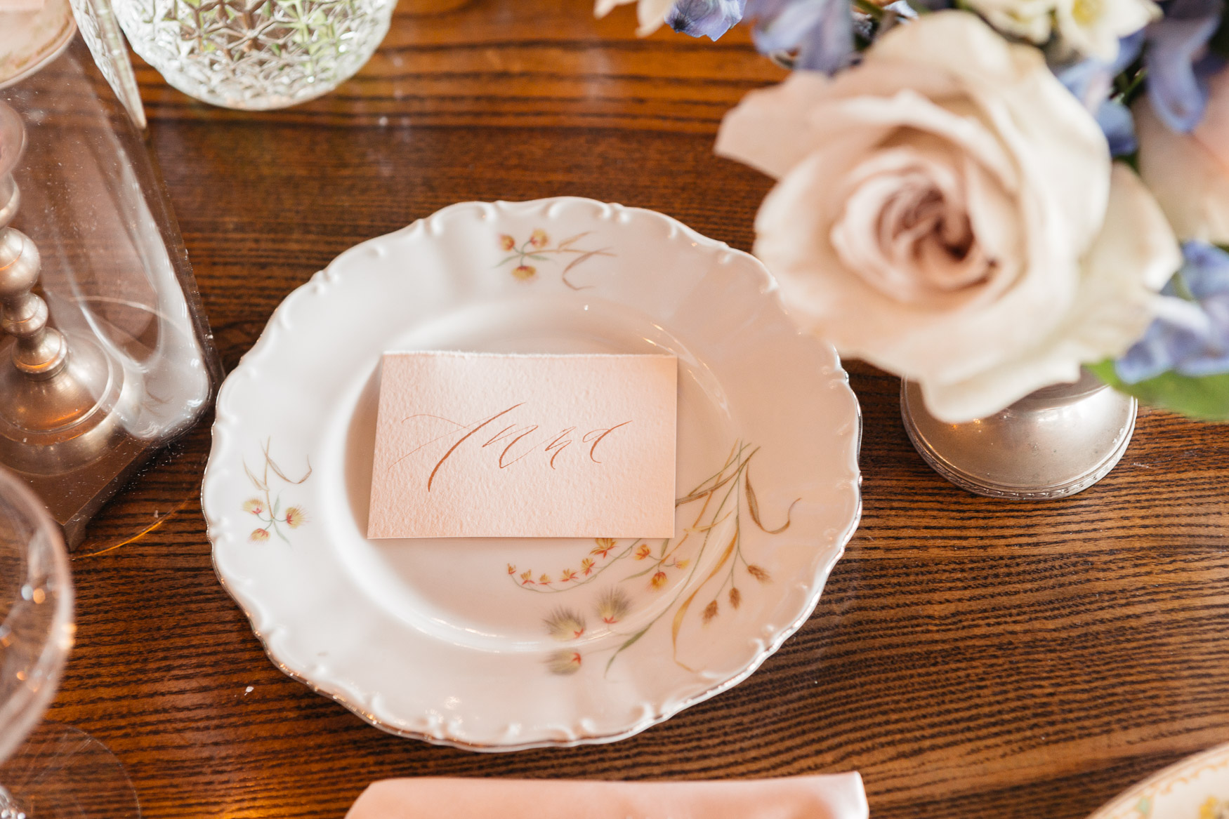feminine copper ink modern calligraphy on blush place card with vintage china and blush garden roses in crystal vases.jpg