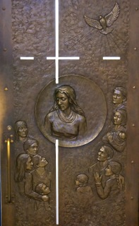 Interior facade of the Holy door: the Virgin Mary and people of Quebec