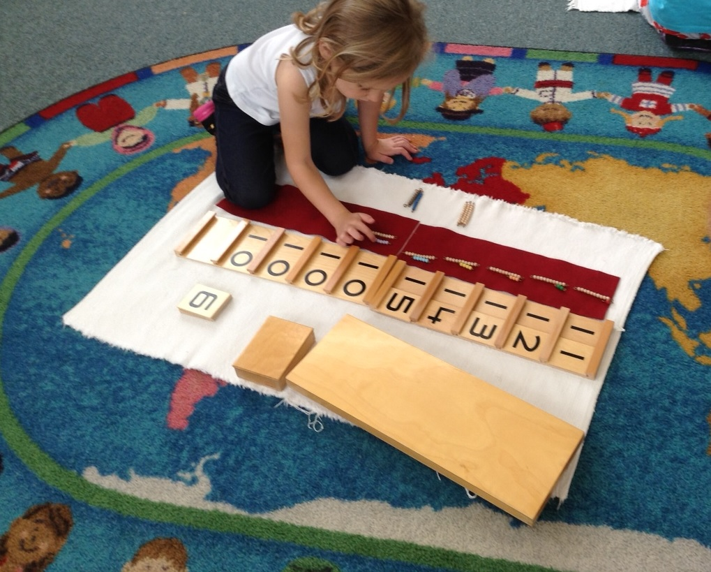 Montessori Pre-School student working on the Teen Boards with Beads activity. The purpose of this activity is to teach sequence, the numbers from 11 to 99.