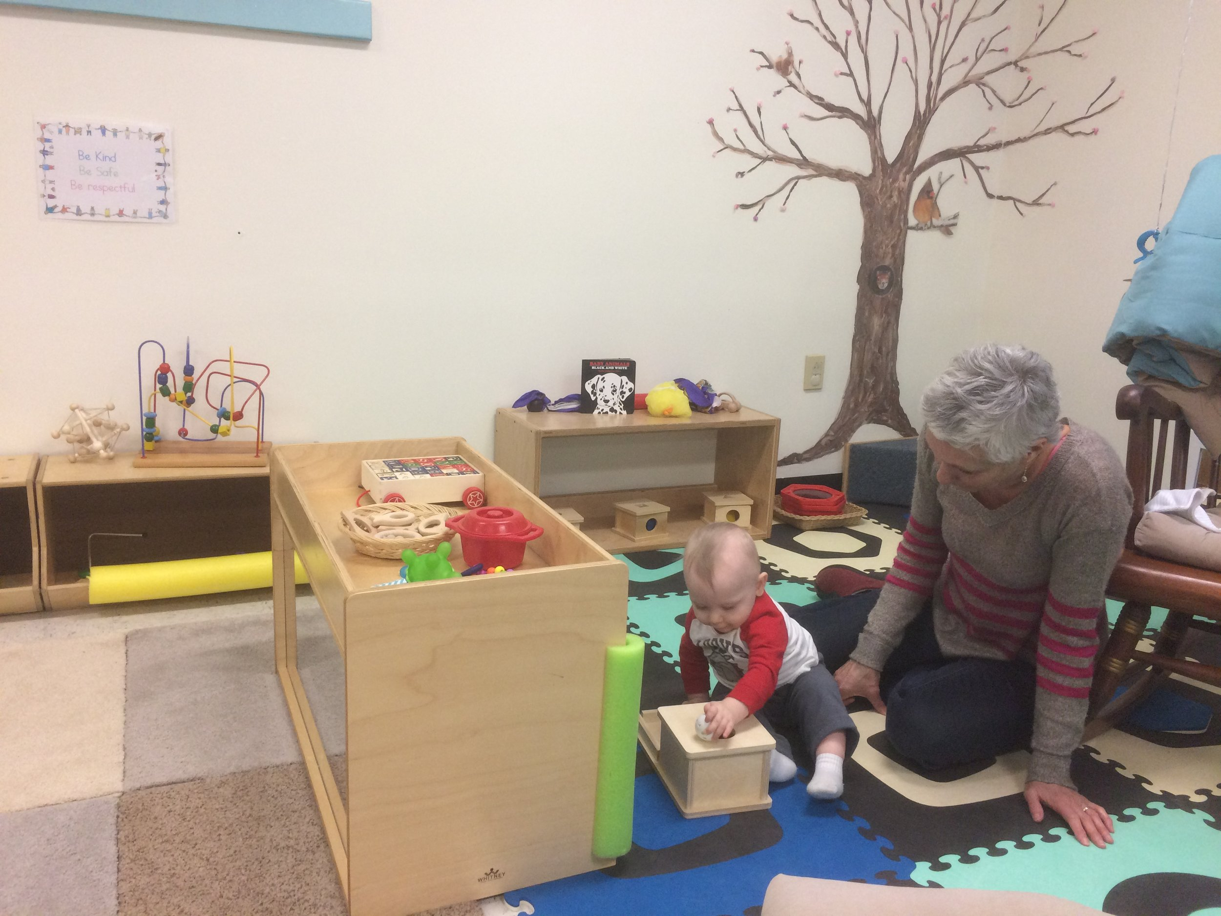 Montessori Toddler student working on the knobbed cylinder block activity. The purpose of this activity is to help develop the child's visual perception of dimension and coordination of movement, as well as strengthen the child's fingers for writing.