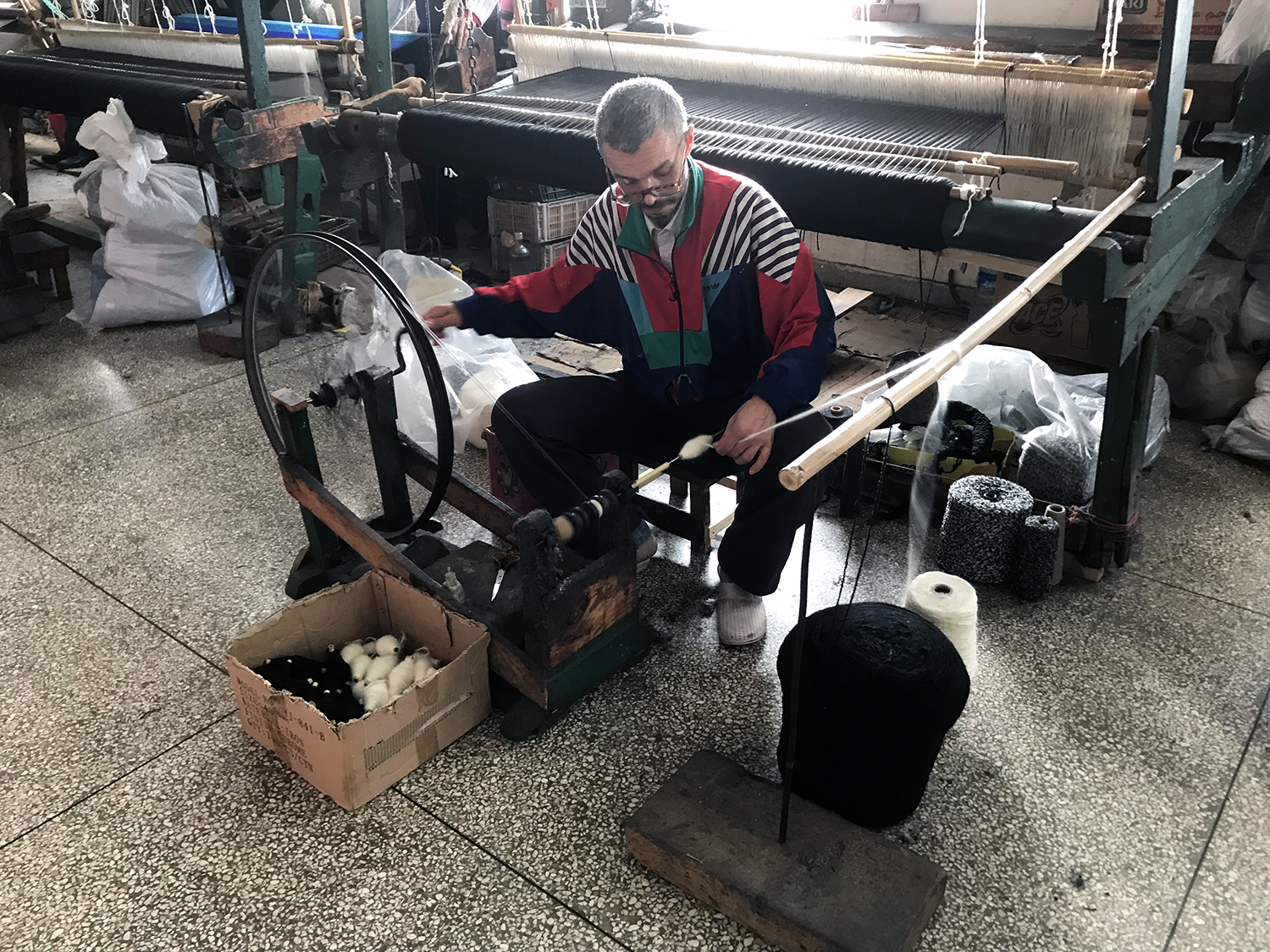 A weaver loading the bobbin with the spinning wheel.