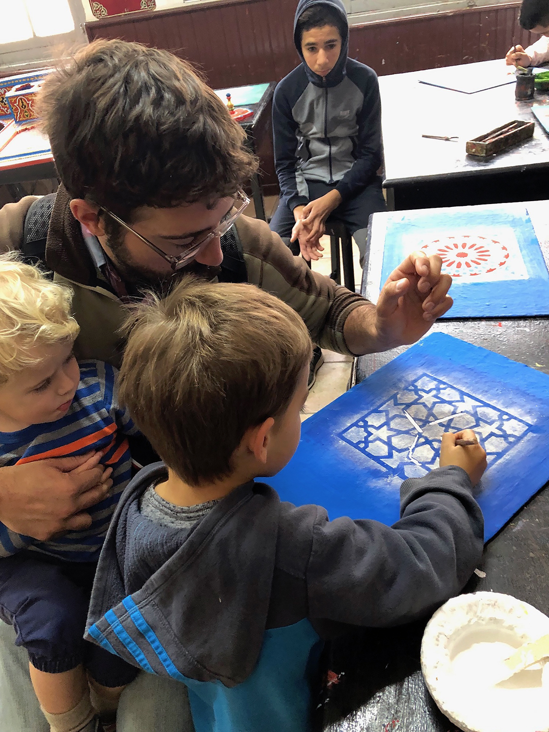 The boys and I get a lesson in Moroccan patterns from the students learning decorative painting