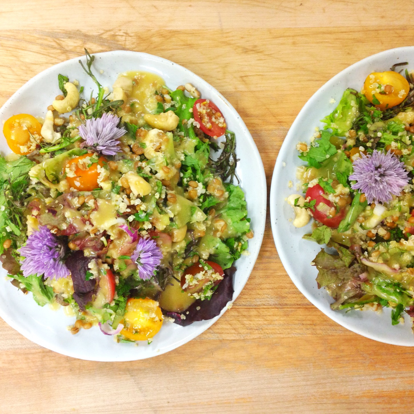 Spicy greens grain salad with chive blossoms