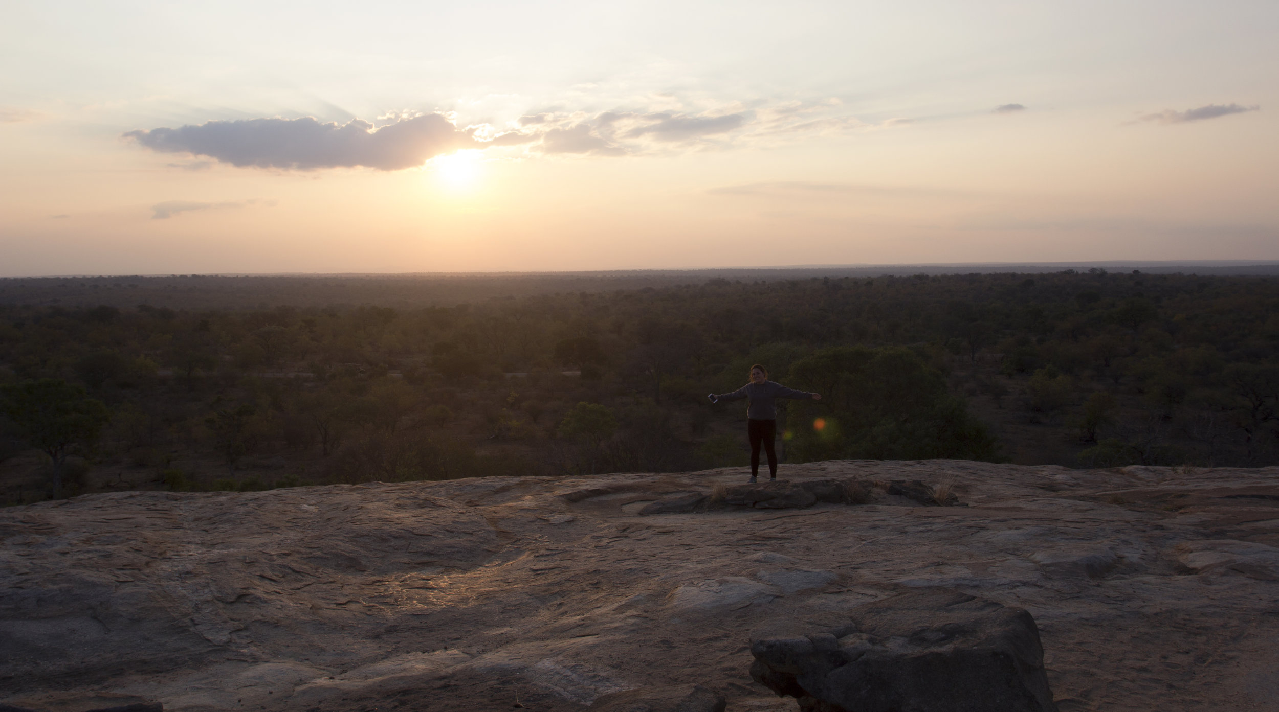 Sunsets - Here is Caroline enjoying the sunset from a great lookout rock near Skukuza Rest Camp, where we slept both nights. We got to watch the sunset and sunrise each day over the beautiful views of the park.