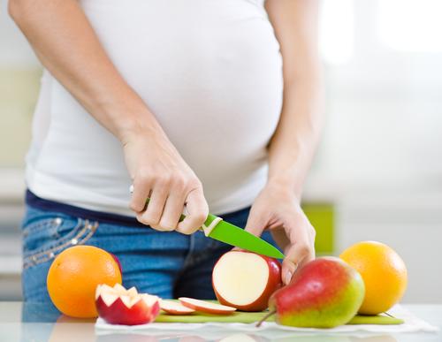 pregnant woman chopping fruit small.jpg
