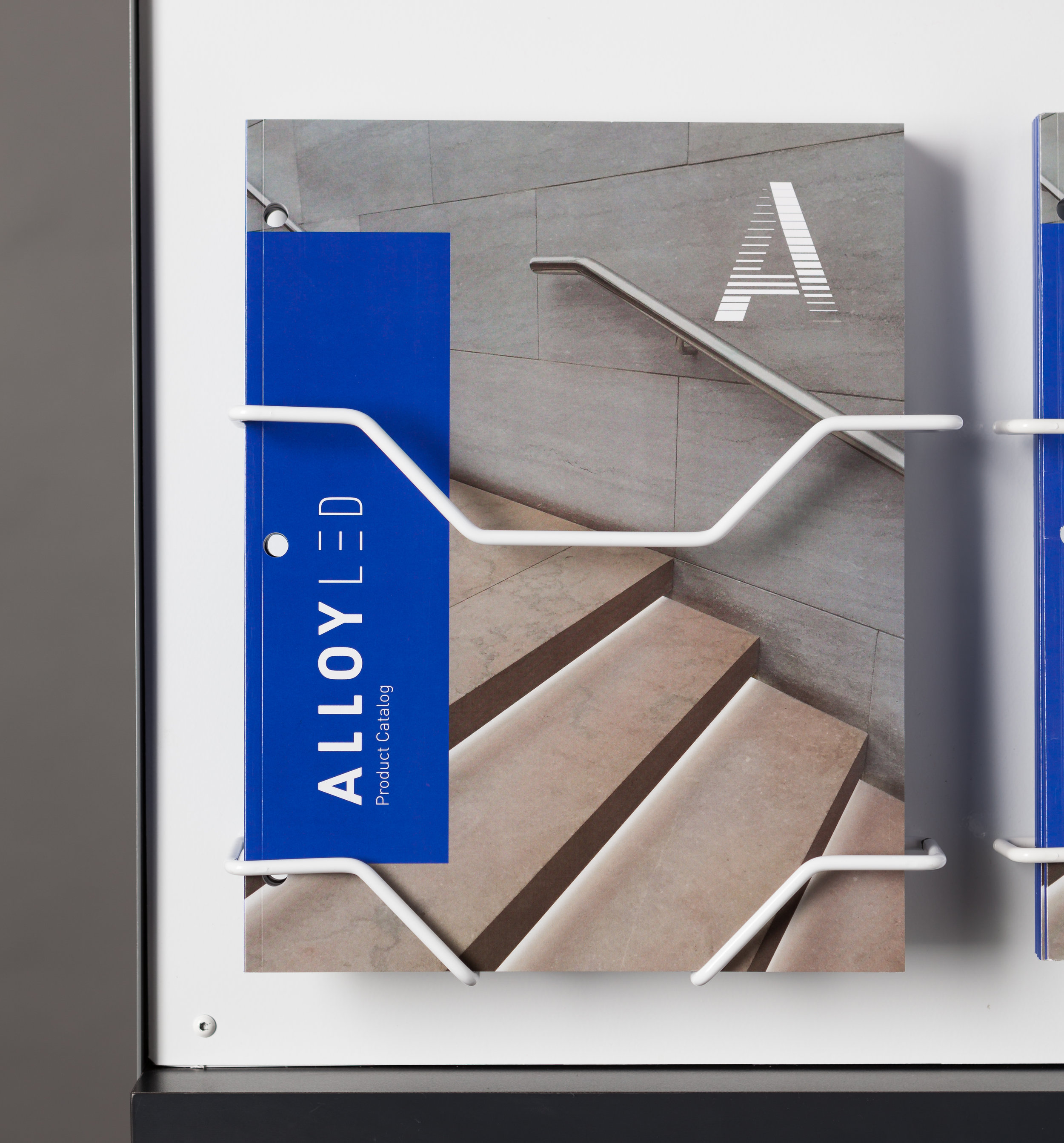 The custom wire brochure holder is modular to the display and also compatible with slat wall and peg wall environments.