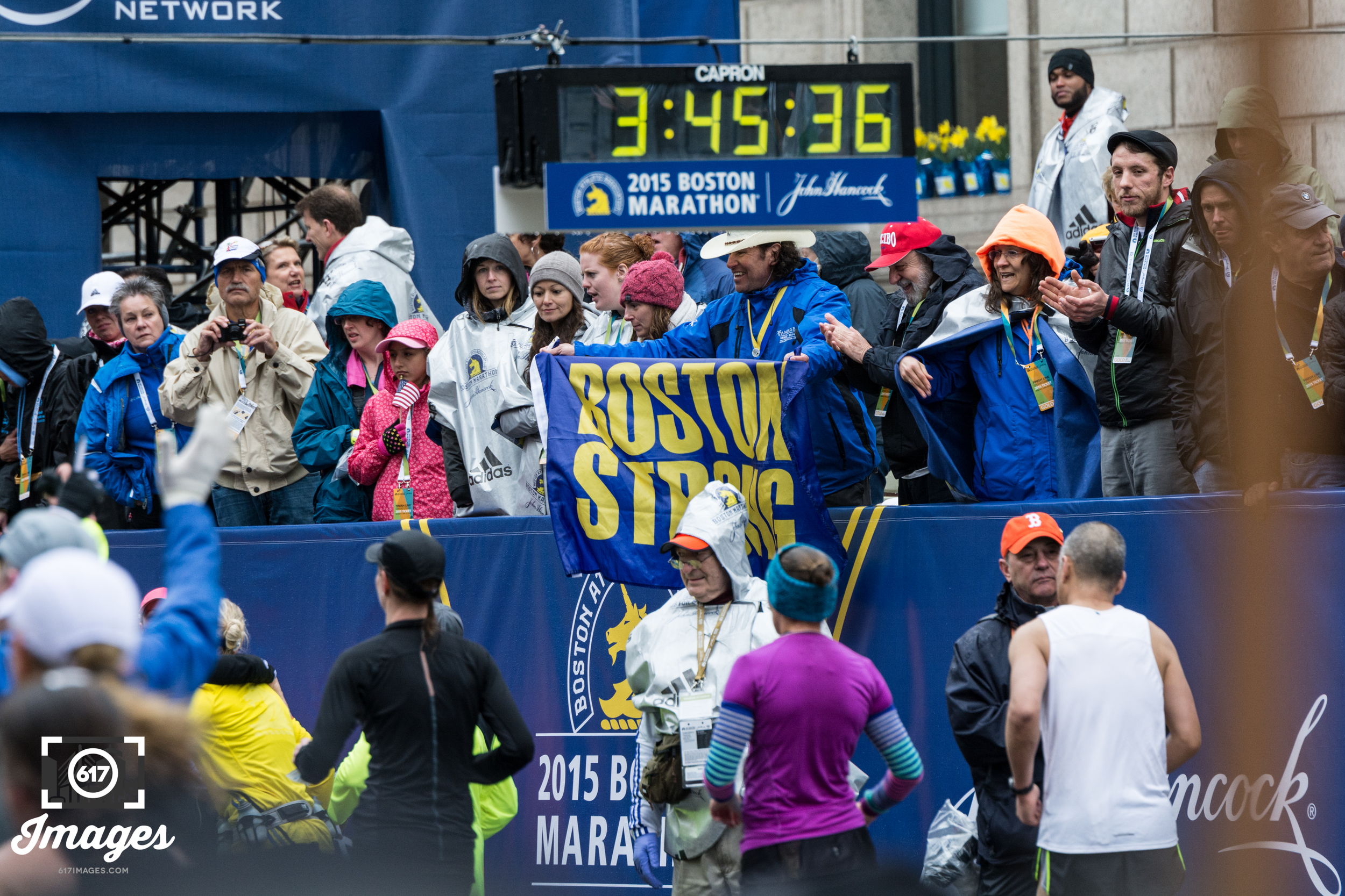 Carlos Arredondo waves his Boston Strong flag as runners cross the finish line.