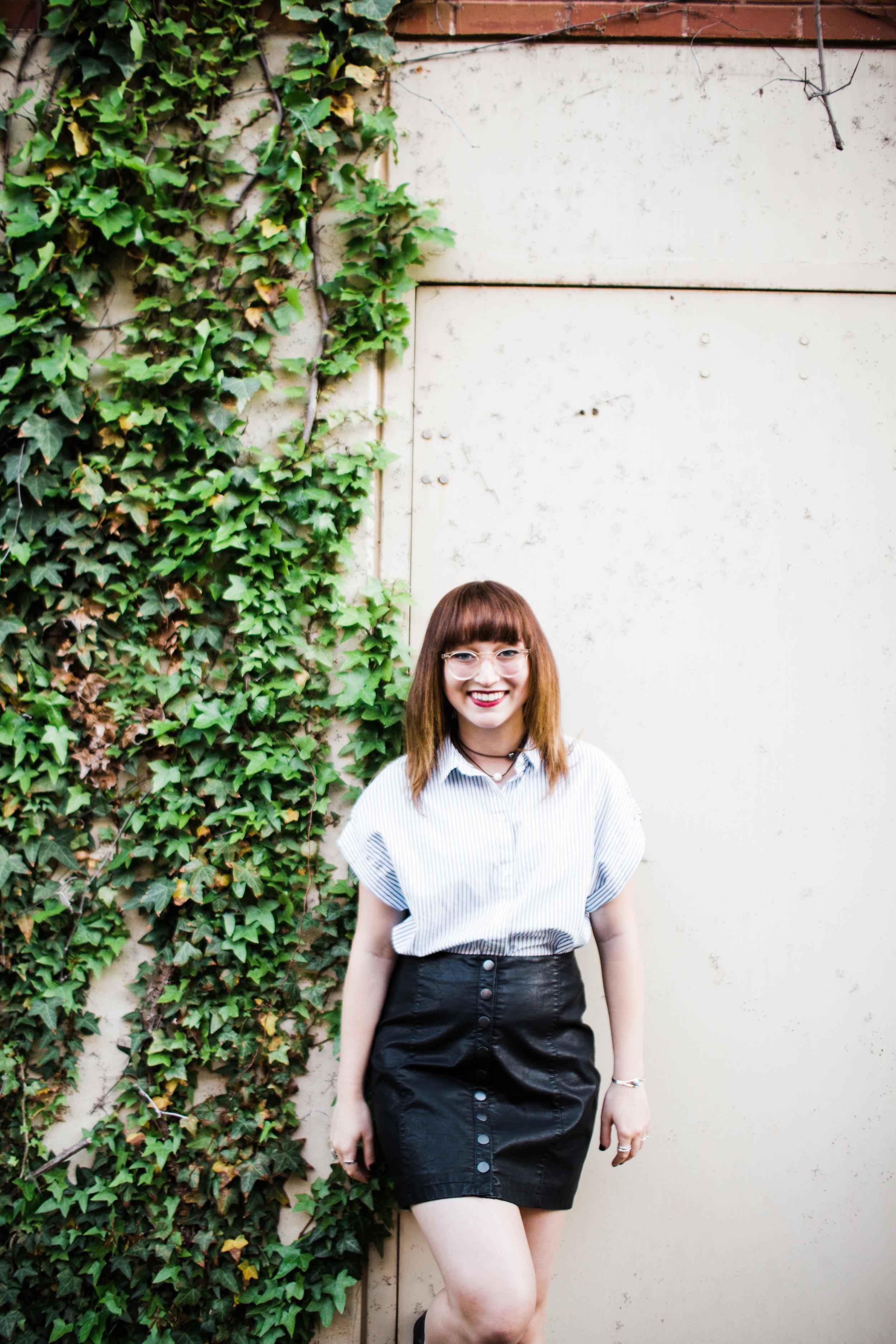 senior girl posing against wall