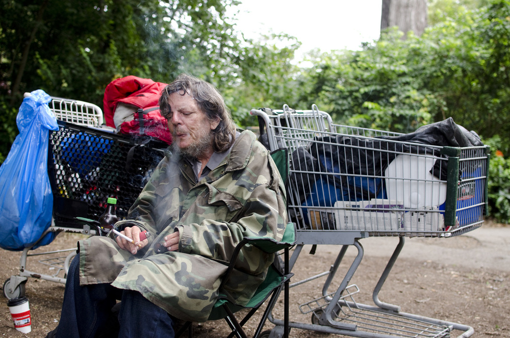 Roy sits with his belongings near Fulton and 7th ave in San Francisco's Golden Gate Park. Roy has been squatting in Golden Gate Park for many of the 10 years that he's been homeless in San Francisco. He likes the park because it's more quiet and comfortable than most places in San Francisco.   Camera Settings: 1/160 f/2.8 iso 320