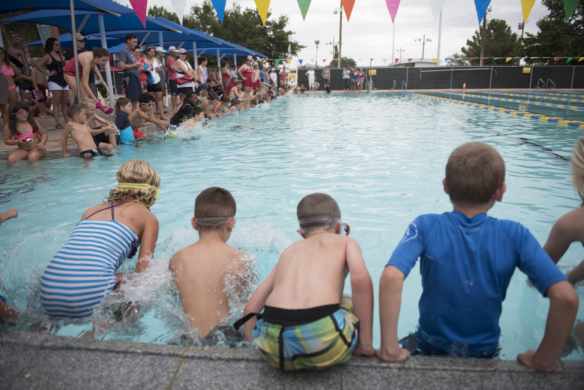 The 9 years old and under league slides into the pool at Broadbent Park Pool for the coin dive during the 67th Annual Boulder City Damboree Celebration in Boulder City, Saturday, July 4, 2015.(JASON OGULNIK/BOULDER CITY REVIEW)