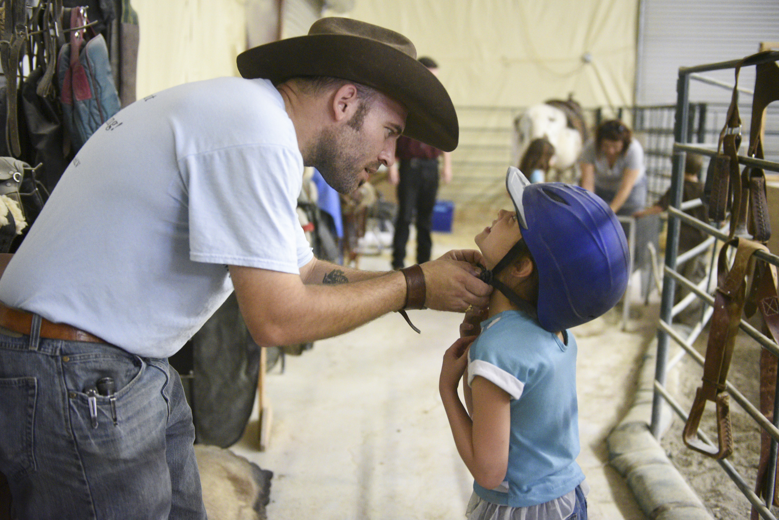 From left, Paul Rogers and Sophia Nola Hudig, 7, try on helmets, looking for a proper fit before Hudig rides the horse, Pocahontas, at Paradise Ranch in Las Vegas, Wednesday, June 3, 2015. Hudig, who has been diagnosed with autism and ADHD, has been part of the Ranch's Horse Assisted Therapy program on a scholarship for three years. (Jason Ogulnik/Las Vegas Review-Journal)