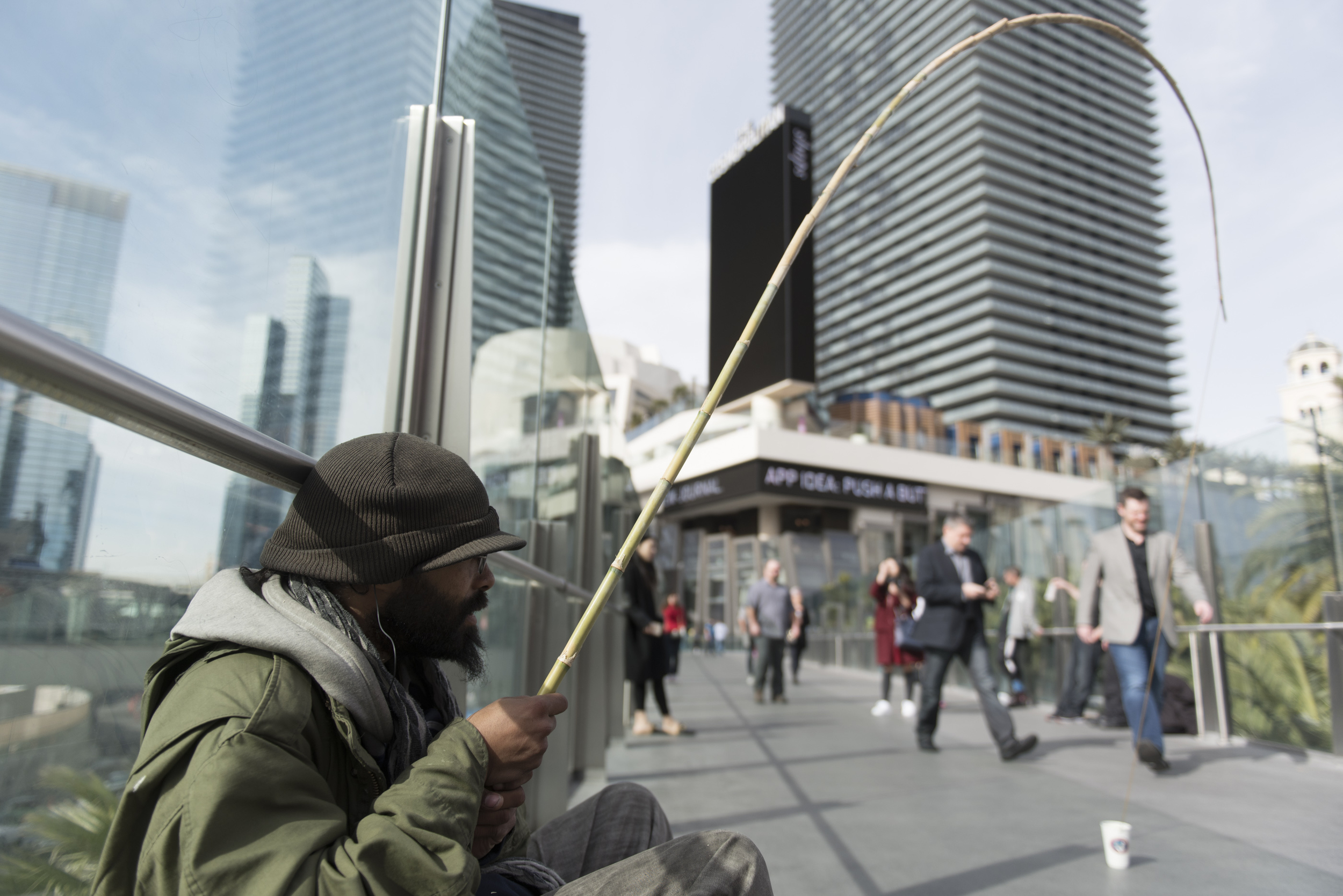 Clarence Witzel panhandles using a set up meant to mimic a fishing rod on the pedestrian overpass at South Las Vegas Boulevard and West Harmon Avenue in Las Vegas Thursday, Jan. 21, 2016. Jason Ogulnik/Las Vegas Review-Journal