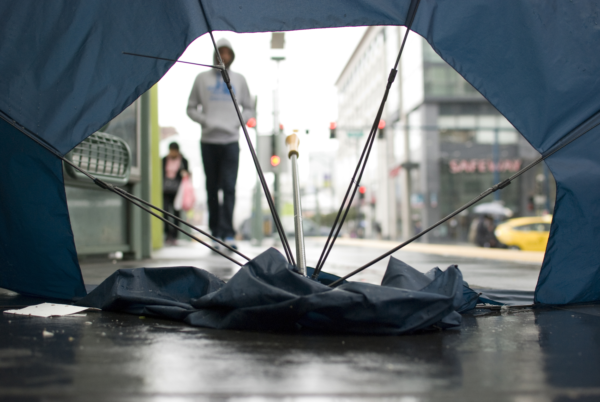 A man walks towards an abandoned, weather-battered umbrella on the outbound side of the K/T light rail platform at 4th Street at King Street in San Francisco's South Beach Wednesday, Mar. 14, 2012.