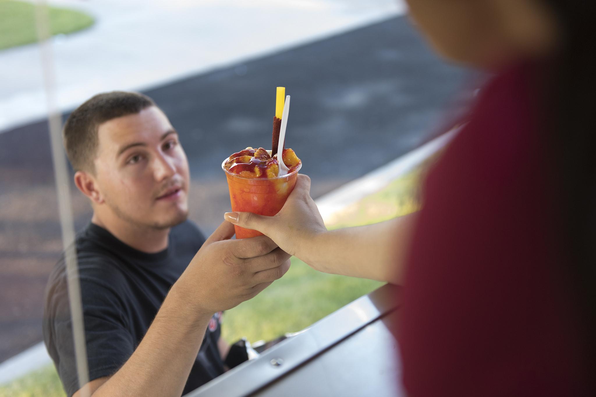 Ryan Silva, left, is handed a mangonada by Amanda Cuadra at Frankie's Ice Cream Trucks at Lewis Family Park in Las Vegas Friday, June 24, 2016. Jason Ogulnik/Las Vegas Review-Journal