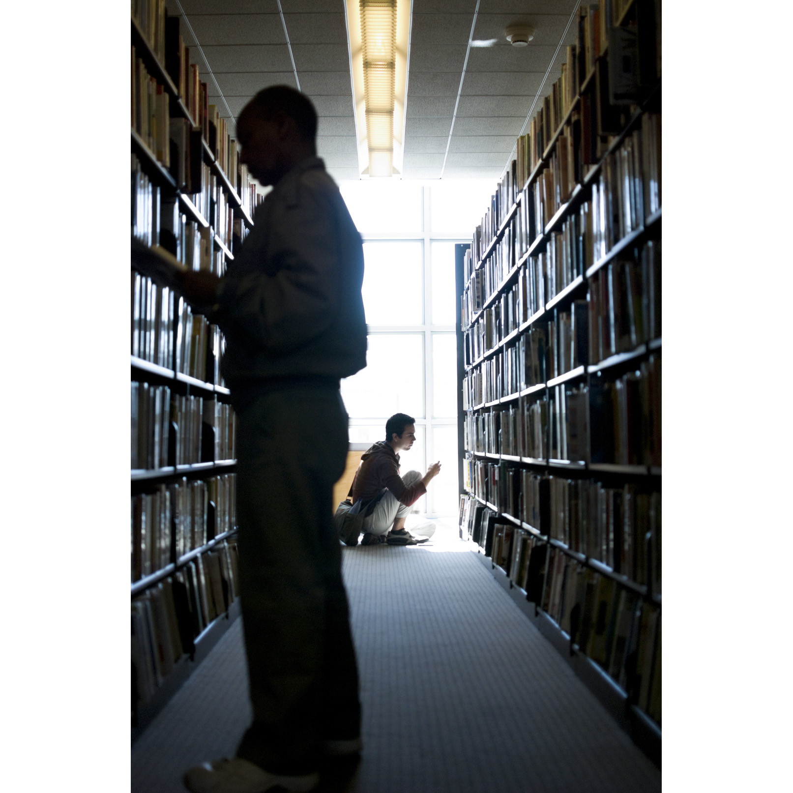 Ike Maldonado, right, looks for exercise books at the San Francisco Public Library's Main Branch.