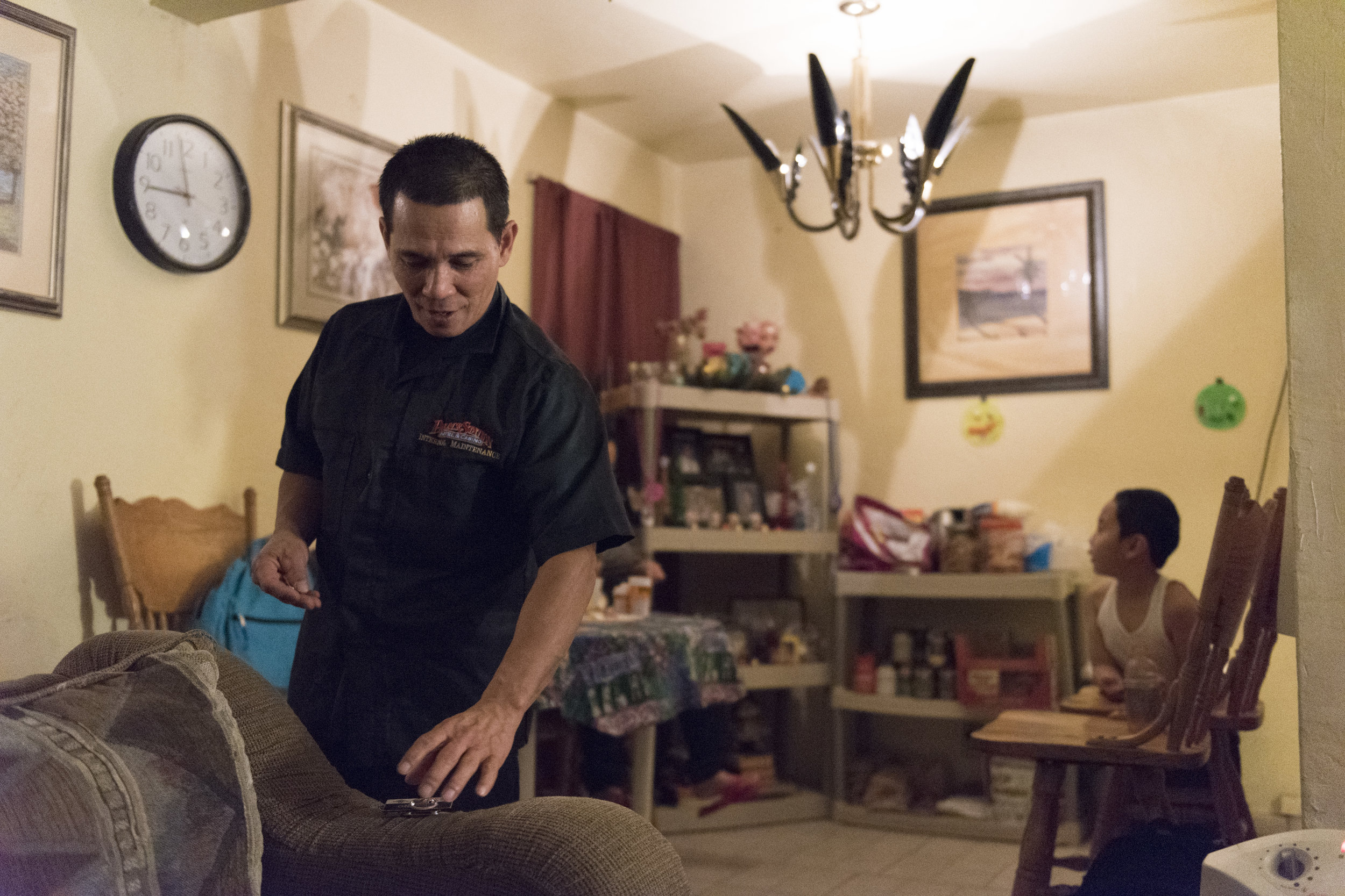 At his home, Casiano Corpus Jr. prepares to put the name tag on his uniform before leaving to work a graveyard shift at Palace Station hotel-casino, a non-union hotel.