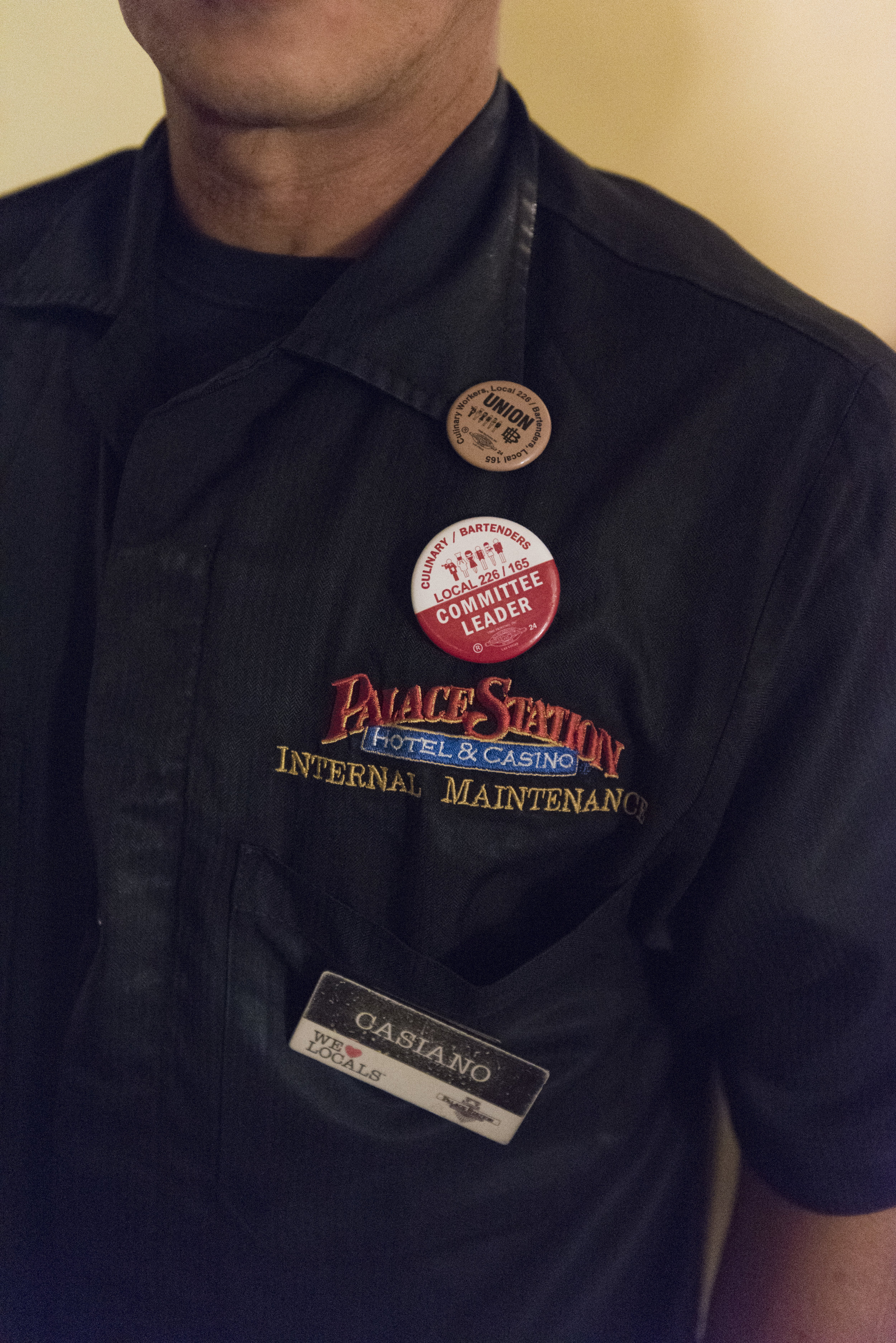 Casiano Corpus Jr., a porter at Palace Station hotel-casino, shows the pro-union buttons on his uniform before leaving to work a graveyard shift at Palace Station hotel-casino. Corpus is a union committee leader, advocating for the hotel to allow a union to be formed.