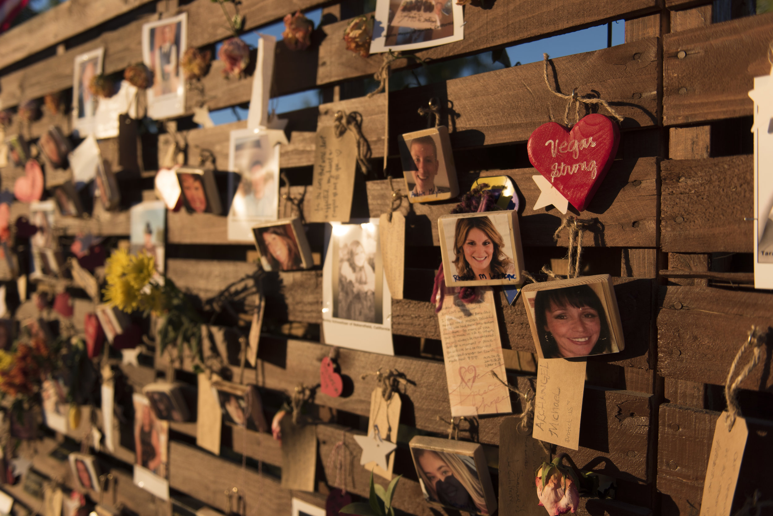 Photos of victims of the Route 91 Harvest Country Music Festival mass shooting are seen on the remembrance wall of the newly opened Las Vegas Community Healing Garden.