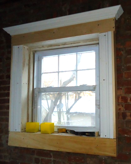 A wooden window frame in the process of being rebuilt.