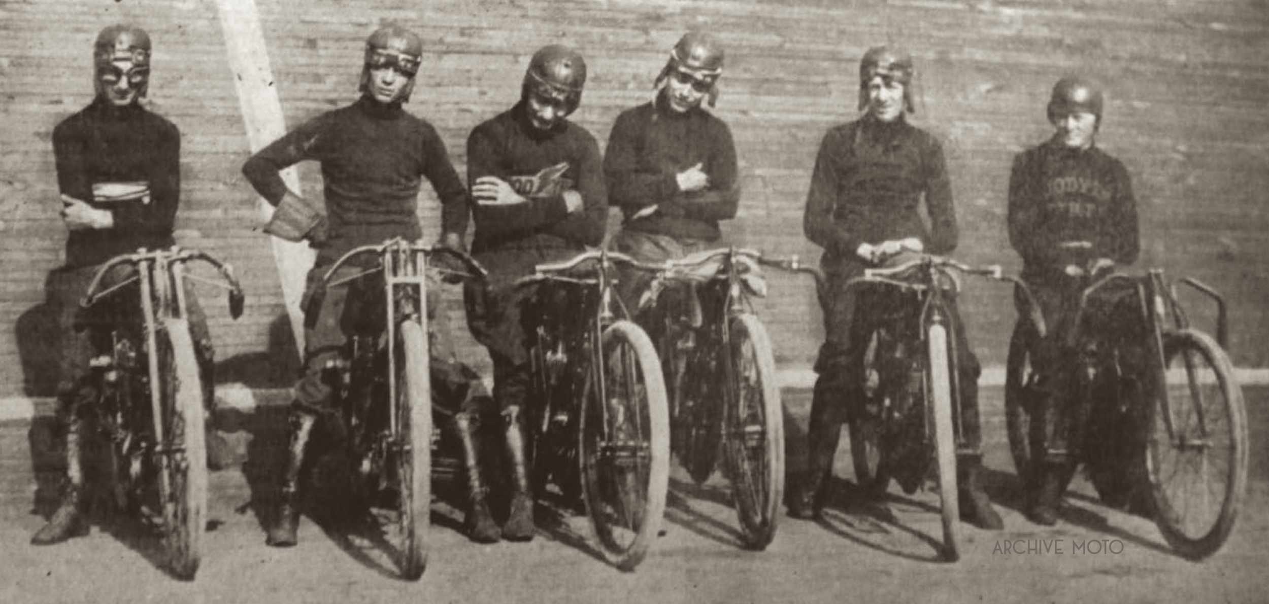 Red Parkhurst is seen here, mounted on an Indian 5th from the left, the track at his back inside the newly constructed Milwaukee Motordrome at the start of the opening season, Summer 1913. Photographed alongside Parkhurst from left to right are Glen Stokes, Jimmy Cox, Eddie Bowen, Danny Armstrong, (Parkhurst), and William Hamilton.
