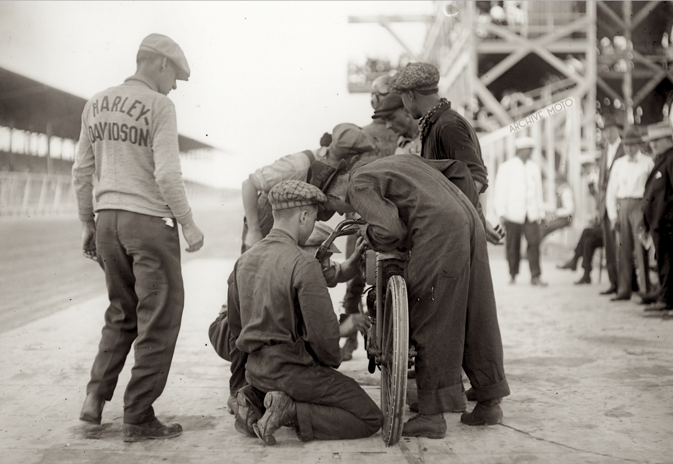 Ottaway's crew outfitted in coveralls provided to all crew members by Firestone for the event working on swapping plugs on Otto Walker's machine  during the 300-Mile race at Chicago's Speedway Park in the fall of 1915.