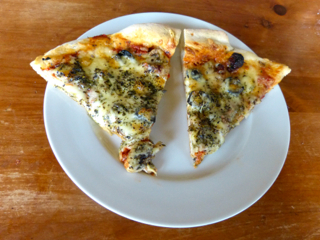 Pizza with mushrooms, black olives, onions, and sun-dried tomatoes. Baked on the Big Green Egg.  Photo by Sue Van Slooten