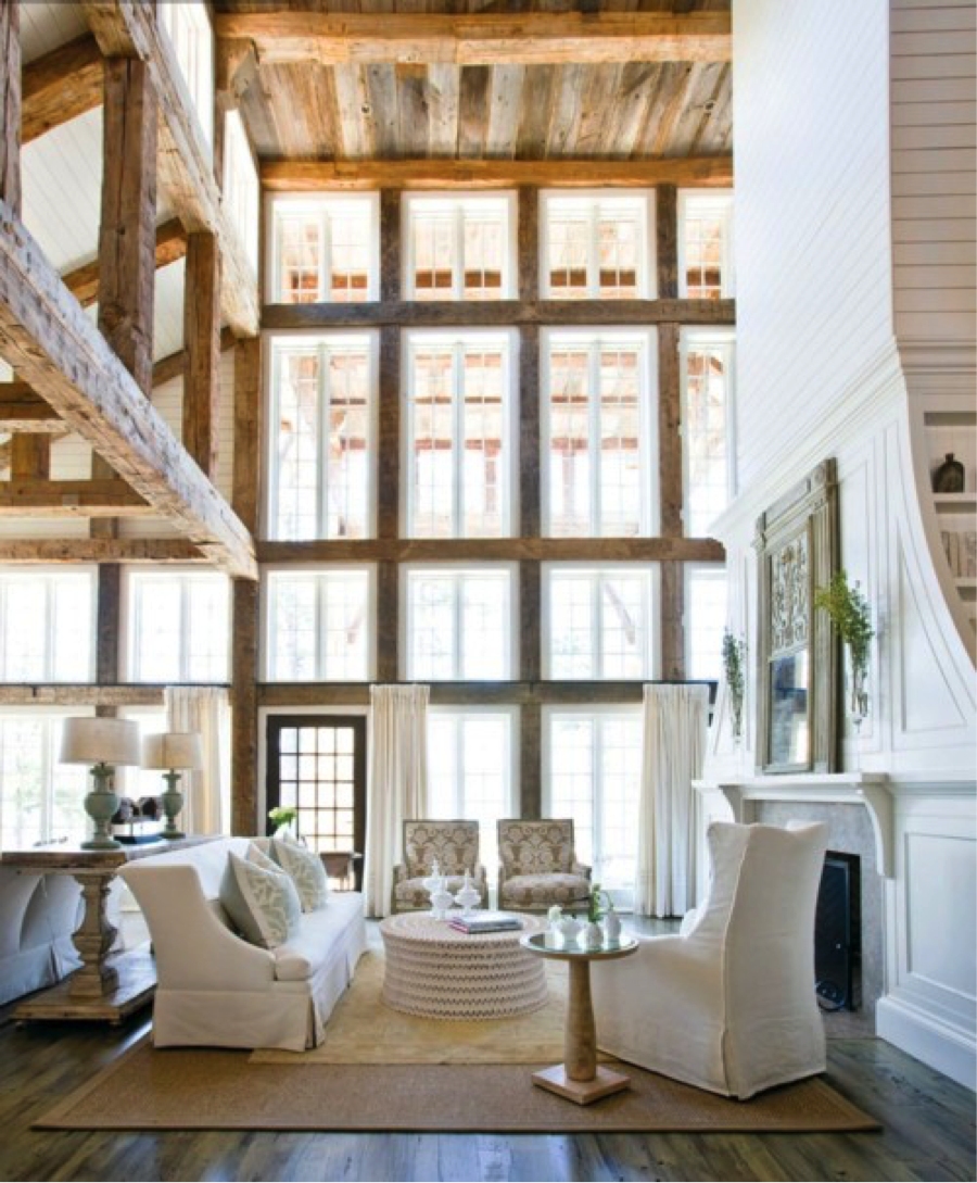 Beautiful rustic house- Tempering an all-white palette with natural wood and stone.Noticethe black door, fire screen and other small details that ground the room. We often think that rustic has to be brown and dark. Nothing could be farther from the truth.