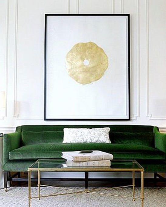 This image speaks to me because it utilizes a neutral - white palette and offsets it with a striking emerald green sofa. The gold accents are just icing on the cake! Now I'm hungry for cake.