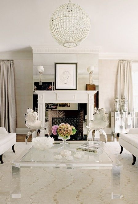 This space shows an interesting application of mirrors - on the fireplace, making it a focal point. Notice the sconces.