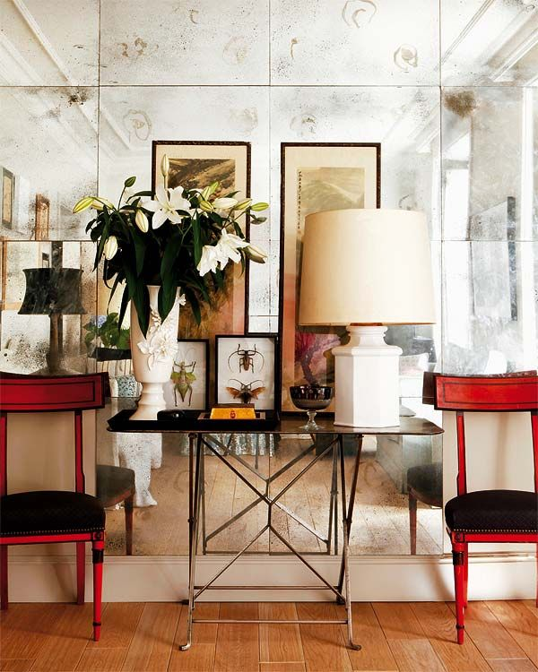 Antique mirror helps make a space look sophisticated and collected. Love the red chairs against the silvery mirrors. The circle effect in the antique mirror is the true way a mirror would silver and age with time.