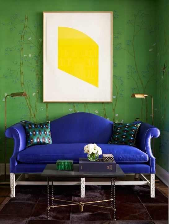 Upholstering a traditional settee in royal blue velvet and contrasted on green walls. The white artwork gives the colorless contrast needed to make this room sing.